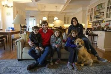 Wyatt (left), Brad, Haley, Lori, and Maddie Ali, in the living room of their new home in Needham — right next door to their old house.